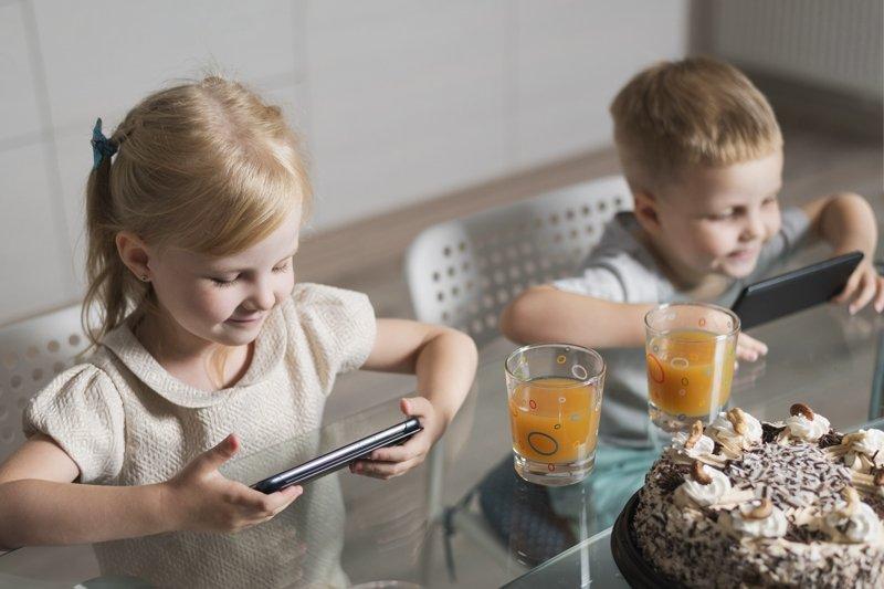 дети за столом с телефоном