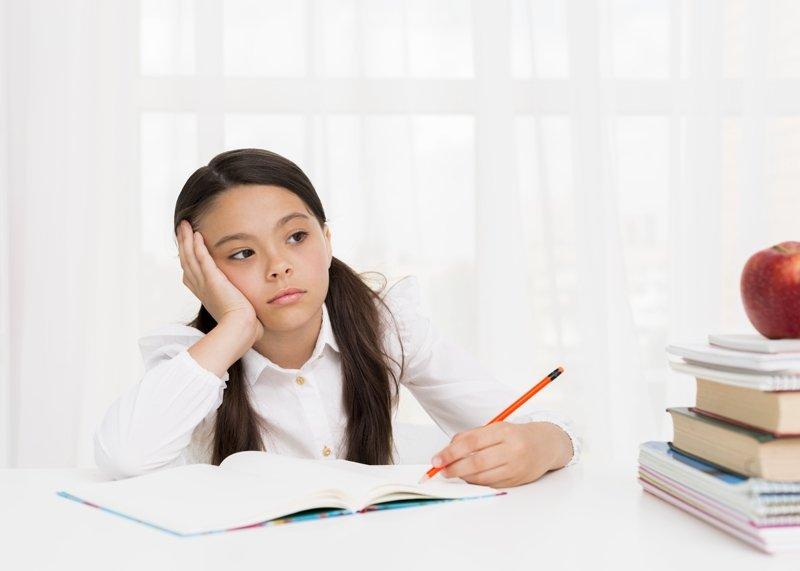 девочка пишет за столом