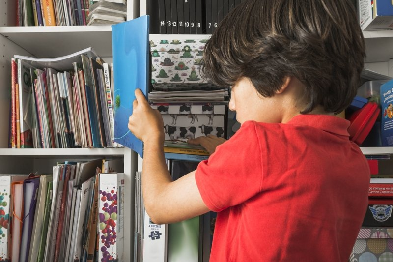 Ребенок убирают книги