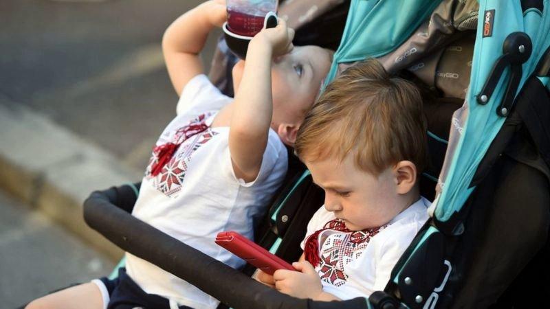 ребенок в коляске с телефоном